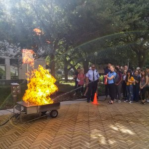 A student puts out a fire while a other students look on during an annual controlled demonstration put on by Fire Prevention Services