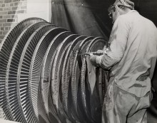 A turbine is being sandblasted by a maintenance worker in this old black & white photograph