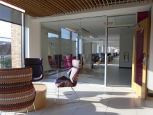 Social and study area in Welch Hall, with researcher seating and lab space beyond the doorway